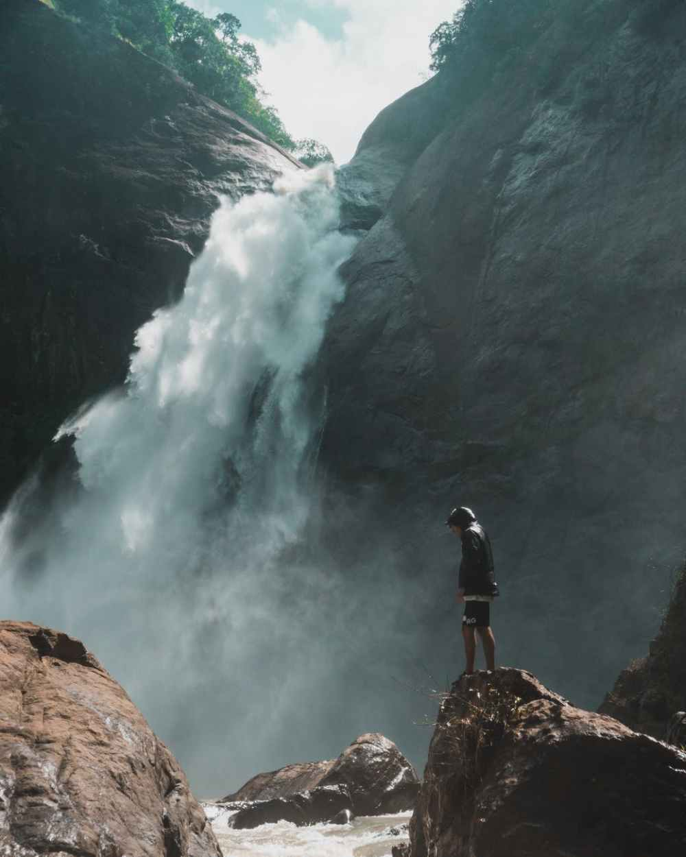 man standing on brown rock cliff in front of waterfalls photography